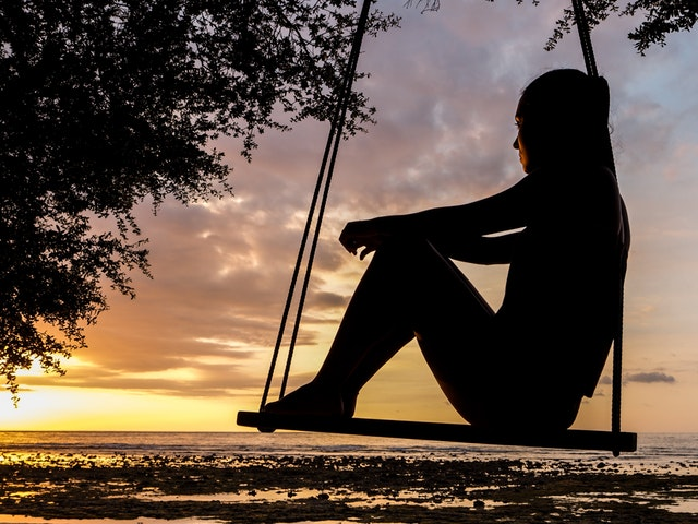 Woman looking at a sunset on a swing thinking about Therapists Psychologists counseling psychological and neuropsychological services in Louisville Kentucky