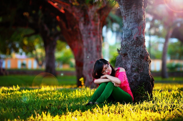 woman sitting under a tree wondering Can I schedule a doctor's appointment on the first visit?